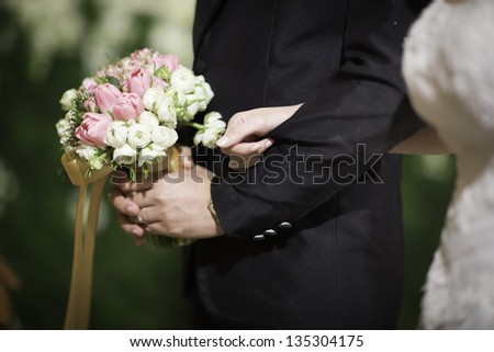 Holding hands of bride and groom