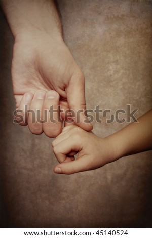 Holding Hands of Love. A father reaches down and holds the hand of his child - stock photo