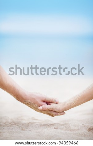 Holding hands on the beach - stock photo