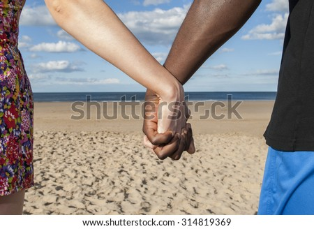 Holding hands part of body showing  male female multicultural sea and sand together love