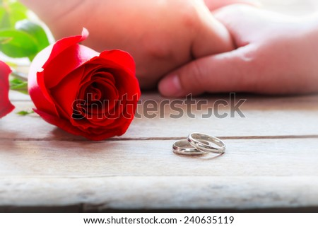 Holding Hands.Red rose with wedding rings on wood table - stock photo