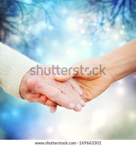 Holding hands with elderly on a blue night background - stock photo