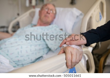 holding hands with elderly patient at hospital