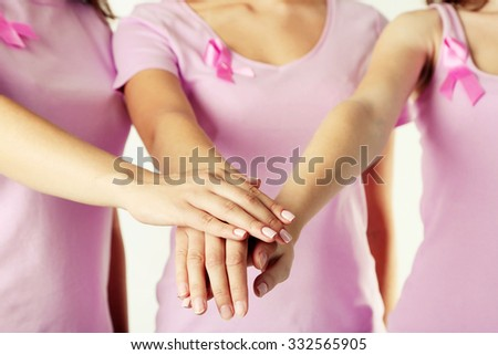 Holding hands women united with breast cancer awareness ribbon - stock photo