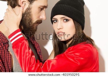 Holding him. Portrait of young attractive hipster couple posing together on white background. - stock photo
