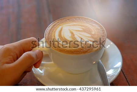 Holding hot coffee latte art,spoon and white plate on wooden background in coffee shop with abstract light  - stock photo