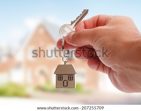 Holding house keys on house shaped keychain in front of a new home - stock photo