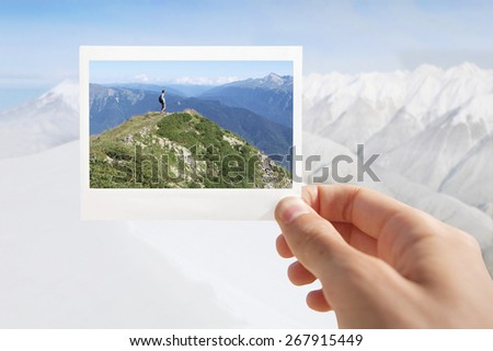 Holding Instant photo on a winter background.