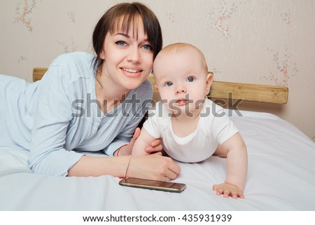 Holding little child, healthy toddler and mom.   Mother and baby closeup portrait, happy faces, Adorable child, mom and kid having fun indoor, parents joy. - stock photo