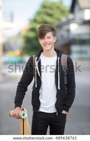 Holding longboard and smiling while wearing a black hoodie.