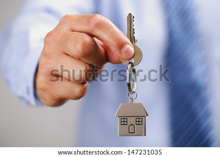 Holding out house keys on a  house shaped keychain - stock photo