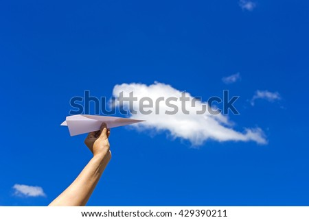 Holding paper airplane before throwing with blue sky background. - stock photo