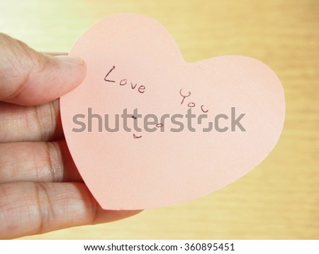Holding pink paper, heart shape with writing ''love you'' word, Valentines day - stock photo