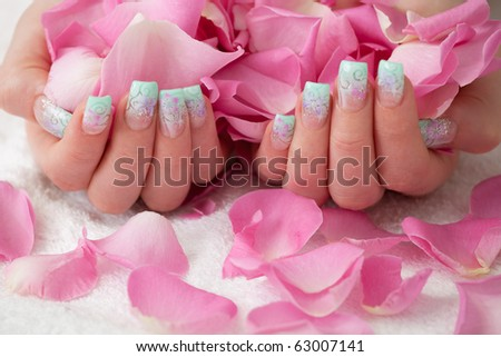 Holding pink rose petals. Artificial fingernail with airbrush pattern