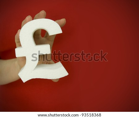 holding pound symbol against a red background - stock photo