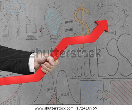 Holding red arrow with business doodles on concrete wall - stock photo