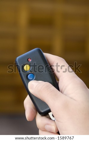 Holding remote control to open garage door - stock photo