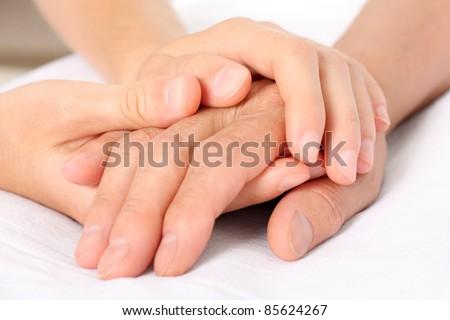 Holding senior hand, giving help - stock photo