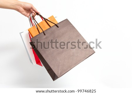 Holding shoping bags by hand on white isolate - stock photo