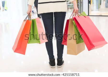 holding shopping bags in various colours, closeup