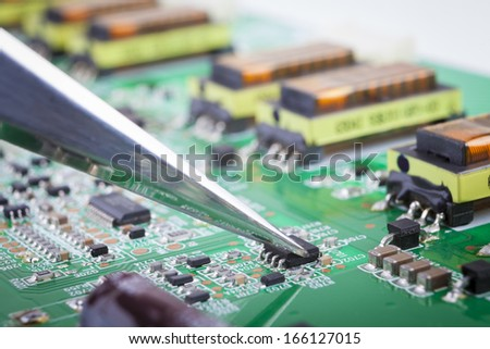 Holding small electronic component with silver metal tweezers on green circuit board - stock photo