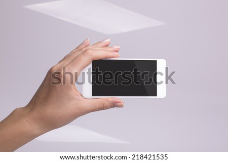Holding smartphone in hand - stock photo