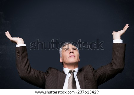 Holding something big and heavy. Confident senior man in formalwear looking up and holding copy space in his hands while standing against blackboard - stock photo