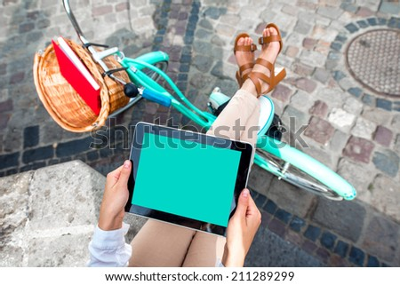 Holding tablet in the hands with bicycle on background in the city - stock photo