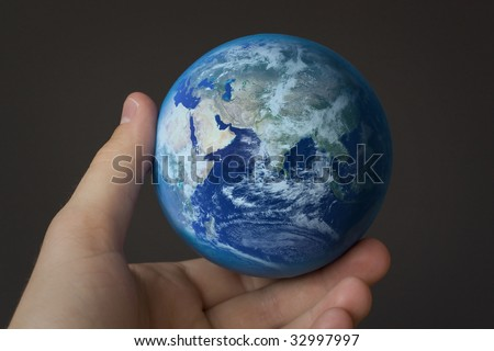 holding the world in my hand in front of a gray background