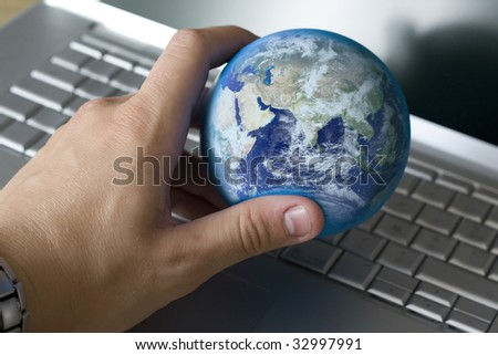 holding the world in my hand in front of a laptop