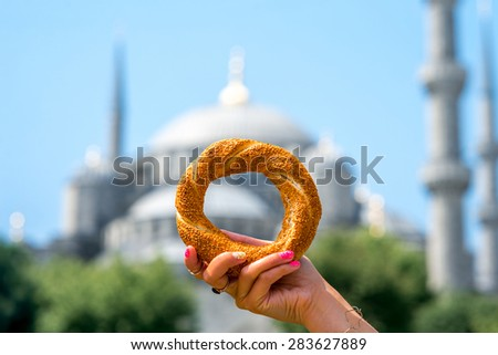 Holding turkish bagel with Blue Mosque on background. Traditional turkish street food. - stock photo