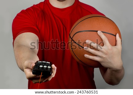 Holding tv remote control and basketball. - stock photo