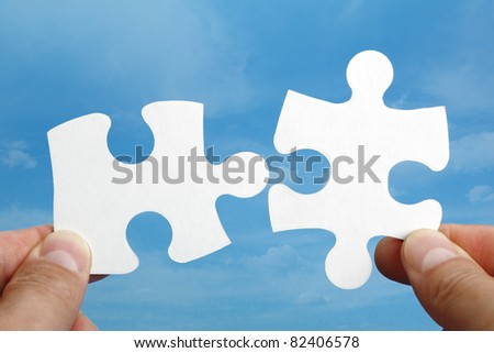 Holding two jigsaw pieces of a blank puzzle trying to fit together against blue sky background - stock photo