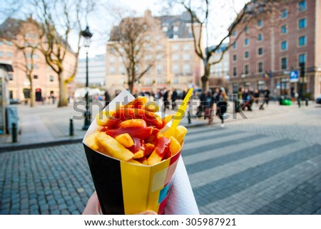 Holding typical belgian fries in hand in the streets of Brussels - stock photo