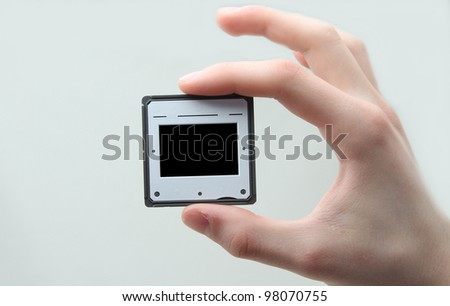 Holding up 35 mm transparancy which shows a black rectangle on which another picture can be placed - stock photo
