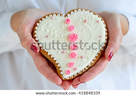 Holding Valentine heart gingerbread cookie - stock photo
