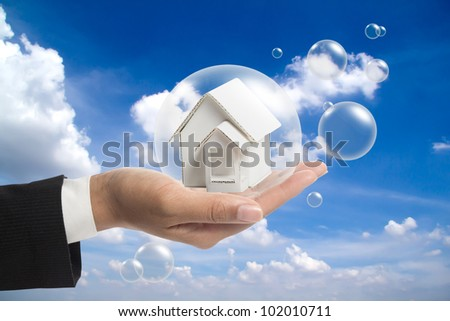 Holding white house in the balls. - stock photo