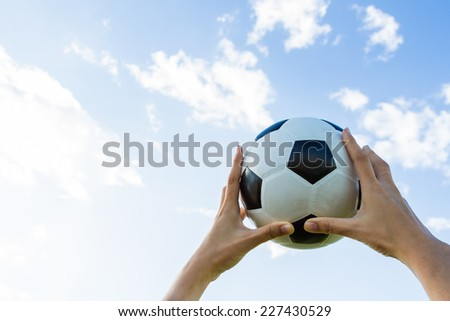 holds a soccer ball in the sky on blue sky background.