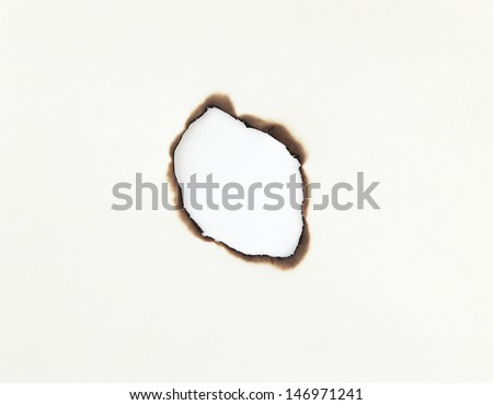 Hole burnt through old paper - stock photo