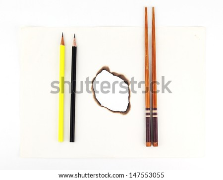 Hole burnt through old paper with pencil and chopsticks on white background - stock photo