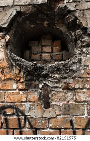 Hole in abandoned brick wall - stock photo