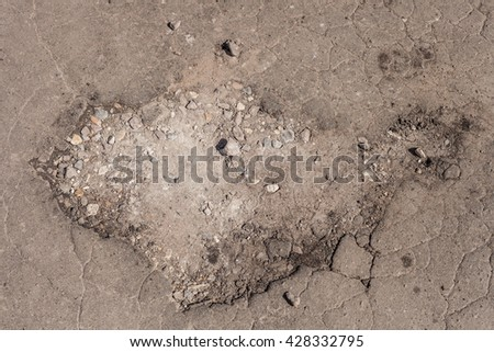 Hole in old corrupt asphalt. Structure of damaged road surface. Texture of broken pavement