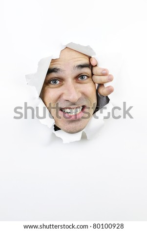 Hole in paper with angry man looking through - stock photo