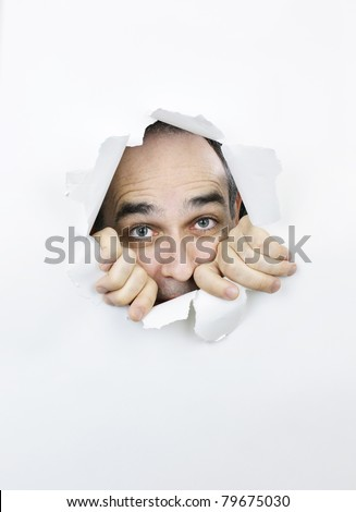 Hole in paper with scared man looking through - stock photo