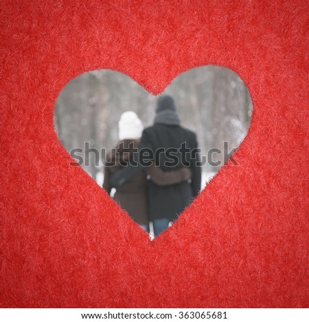Hole in shape of heart. Plot is Valentines Day. A loving couple embracing in defocusing - stock photo