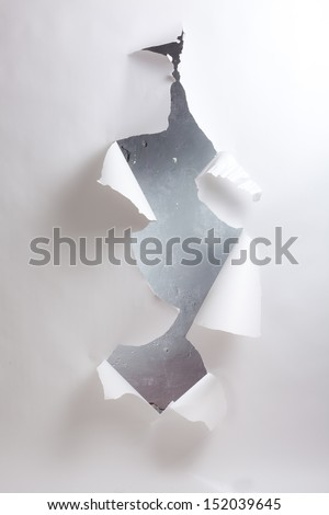 Hole in the paper with torn edges. - stock photo