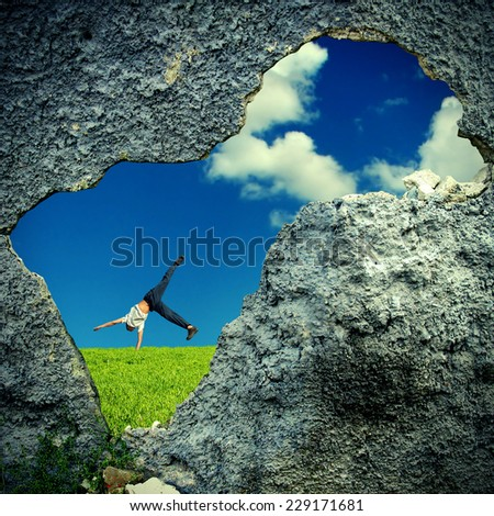 Hole in the Wall into Nature Landscape with Somersault of Teenage Boy - stock photo