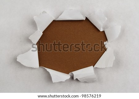 Hole ripped in paper on brown background - stock photo