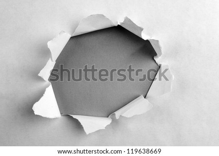 Hole ripped in paper on grey