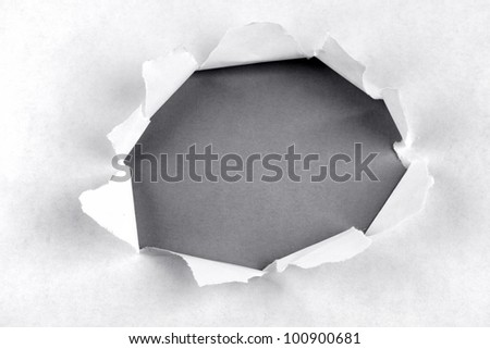 Hole ripped in paper on grey background - stock photo